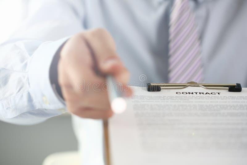 Brazo masculino en forma del contrato de la oferta del traje encendido foto de archivo