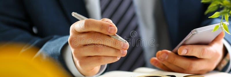 Brazo masculino en pluma del teléfono y de la plata del control del traje fotografía de archivo