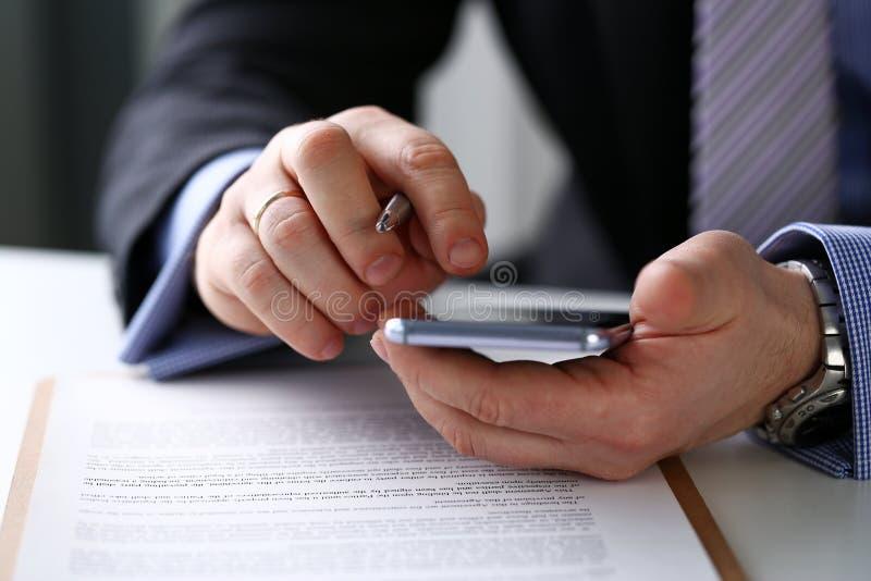 Brazo masculino en pluma del teléfono y de la plata del control del traje en el primer del lugar de trabajo fotos de archivo