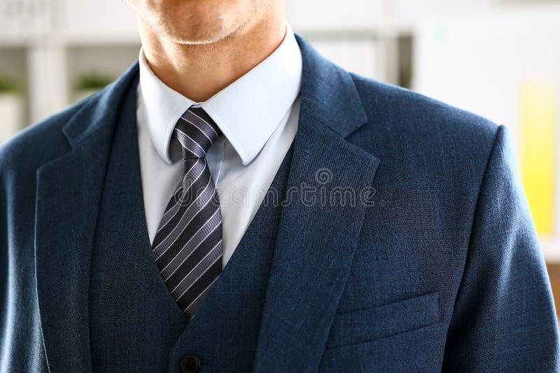Brazo masculino en primer determinado del lazo del traje azul fotografía de archivo