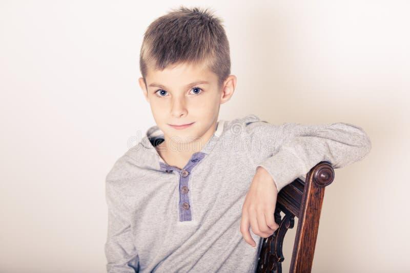 Brazo que se inclina asentado del muchacho lindo en la parte de atrás de una silla imagenes de archivo
