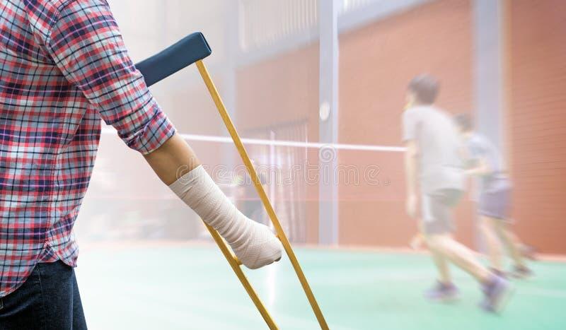 Brazo y pierna dolorosos de la mujer de lesión con el vendaje de la gasa y el wo con imagen de archivo