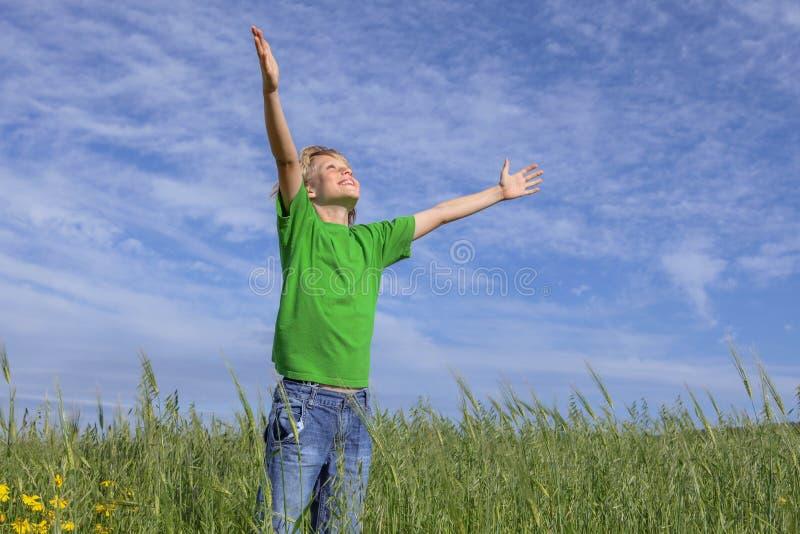 Brazos cristianos felices del muchacho aumentados en rezo foto de archivo libre de regalías