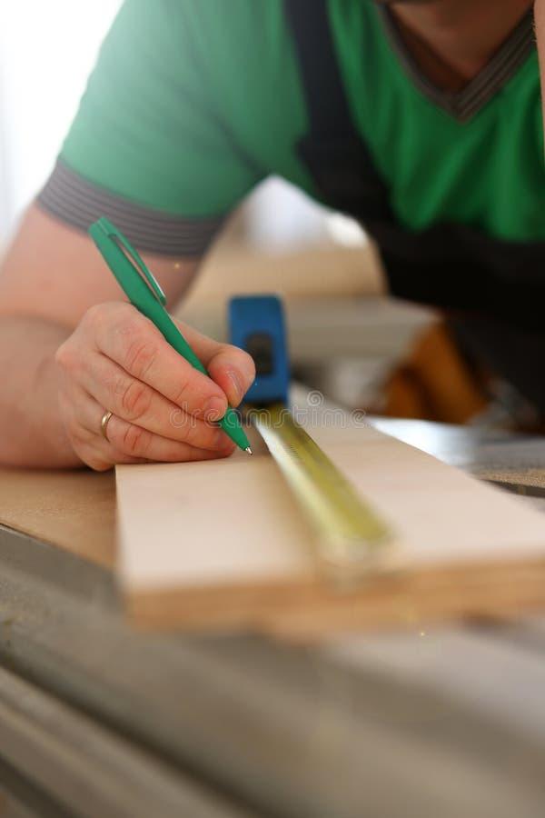 Brazos del trabajador que miden el primer de madera de la barra imagenes de archivo