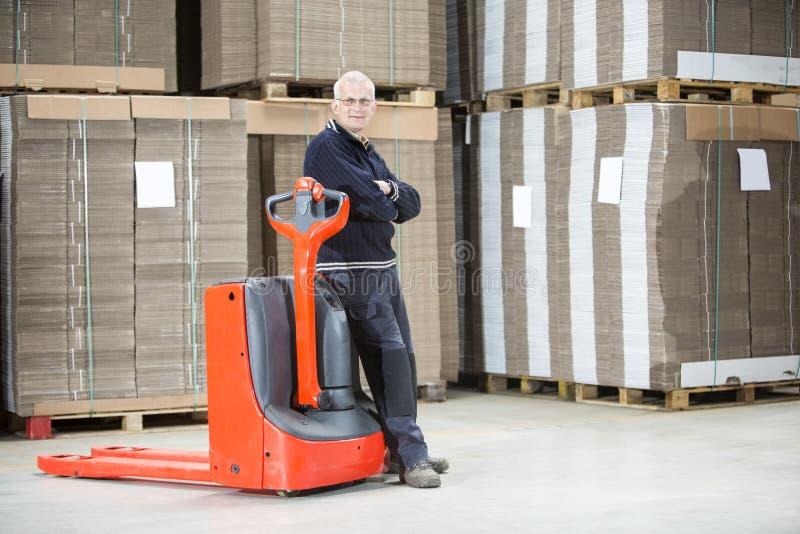 Brazos derechos del trabajador cruzados en Warehouse imagen de archivo