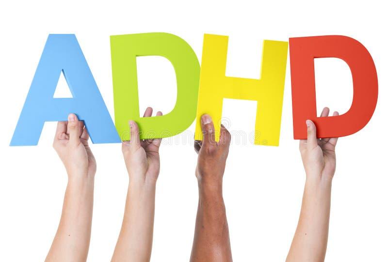 Brazos multiétnicos aumentados sosteniendo ADHD fotos de archivo libres de regalías