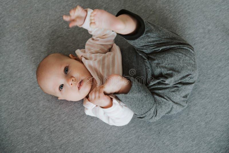 Brazos y piernas que estiran recién nacidos en el piso, visión superior fotografía de archivo libre de regalías