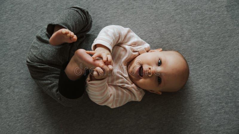 Brazos y piernas que estiran reci?n nacidos en el piso, visi?n superior fotos de archivo libres de regalías