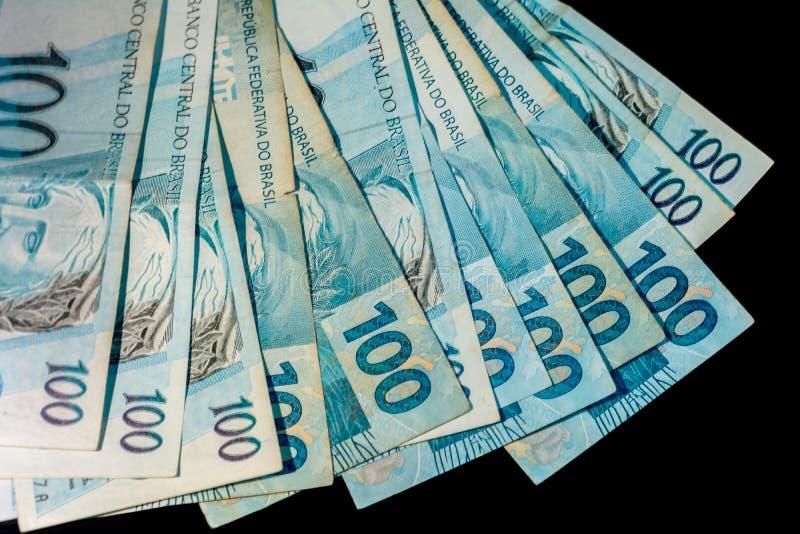 Brazylijscy pieniądze sto rachunki odizolowywający na czarnym tle obrazy stock