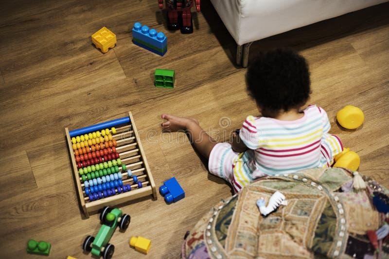 Brazylijska berbeć dziewczyna bawić się drewniane zabawki na podłoga fotografia royalty free