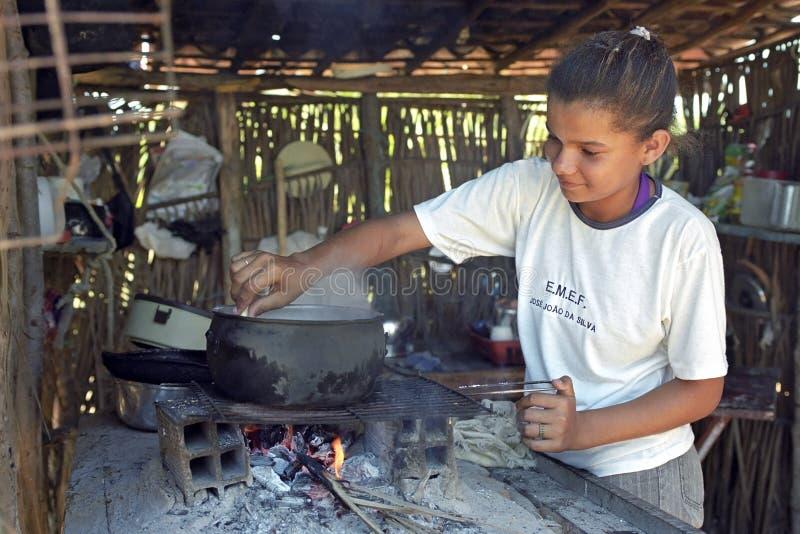 Brazylijska dziewczyna gotuje na drewnianym ogieniu z łupką obrazy stock