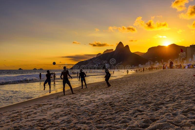 Brazylijski chłopiec sztuki futbol na Ipanema plaży przy zmierzchem w Rio De Janeiro zdjęcia royalty free