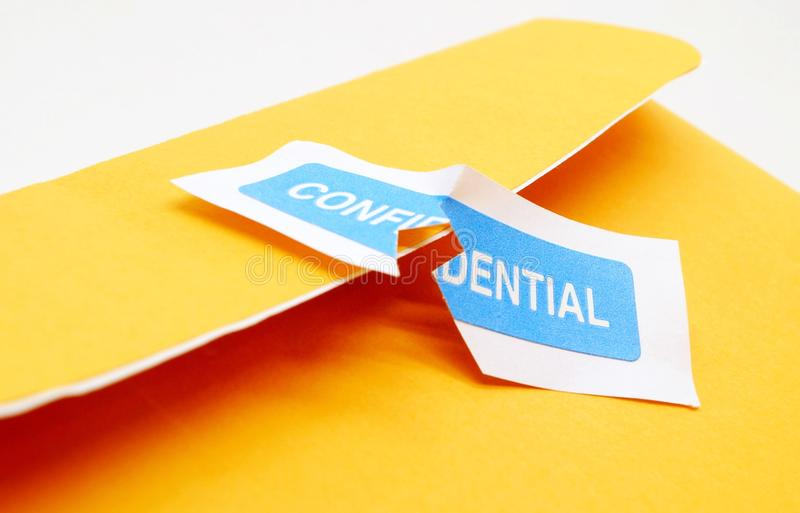 Breach of Trust. A Confidential file ripped open representing a violation of privacy royalty free stock photo