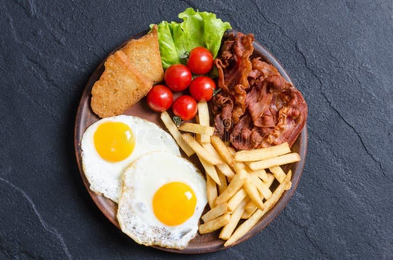 Breackfast: fransmansmåfiskar, bacon och stekte ägg arkivfoto