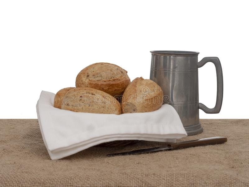 Bread and ale, rustic lunch, with old pewter tankard, bread rolls and knife. Still life. Bread and ale, rustic lunch, with old pewter tankard, wholemeal bread royalty free stock photos