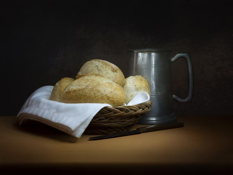 Bread and ale, rustic lunch, with old pewter tankard, bread rolls and knife. Painting like chiaroscuro still life. Bread and ale, rustic lunch, with old pewter stock image