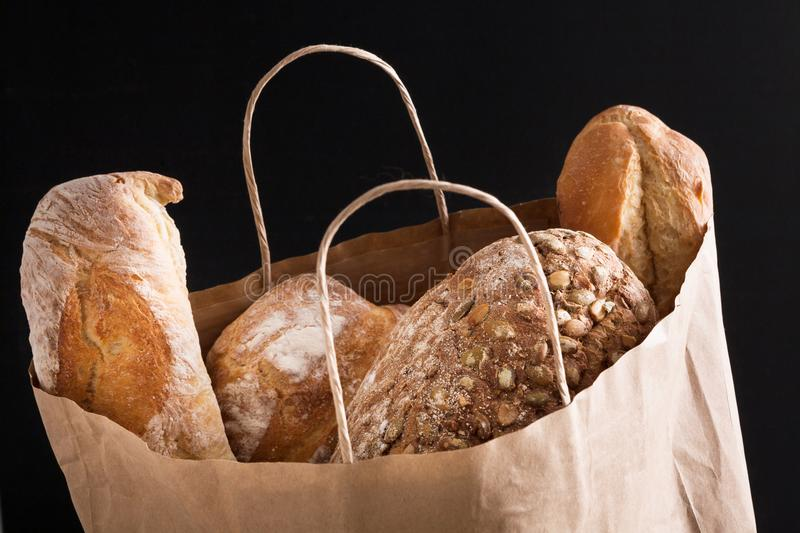 Paper bag with bread assortment at black background royalty free stock photography