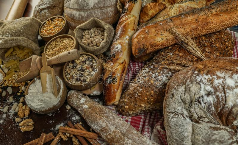 Bread background. Brown and white whole grain loaves wrapped in kraft paper composition on rustic dark wood with wheat ears scatte stock photography