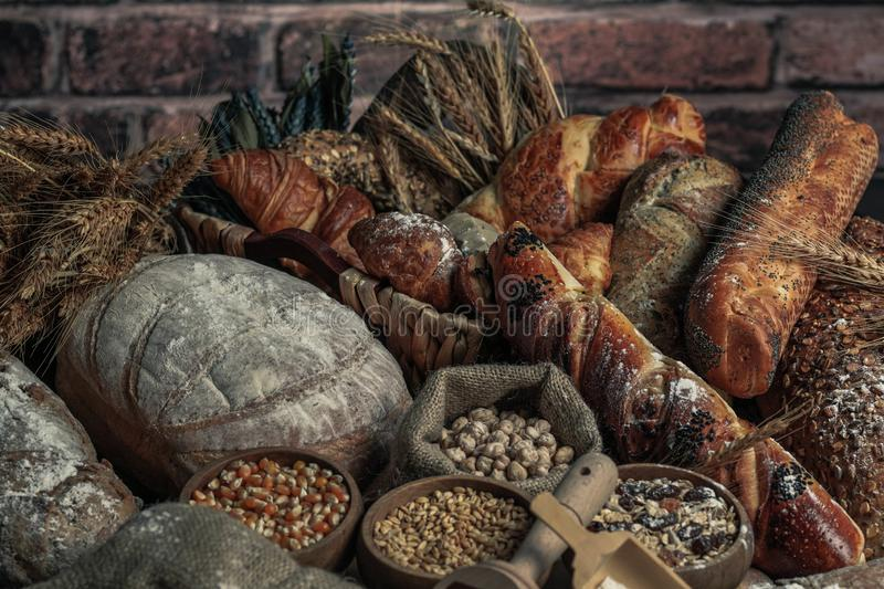 Bread background. Brown and white whole grain loaves wrapped in kraft paper composition on rustic dark wood with wheat ears scatte stock photos
