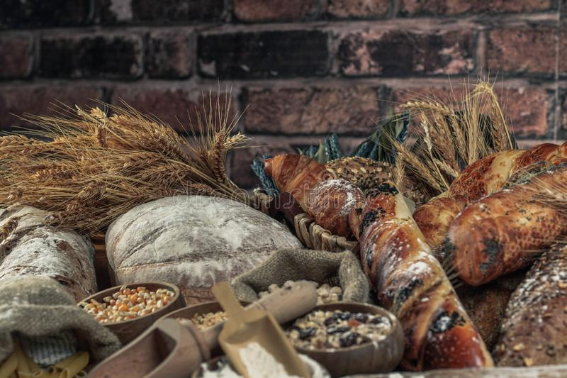 Bread background. Brown and white whole grain loaves wrapped in kraft paper composition on rustic dark wood with wheat ears scatte stock images
