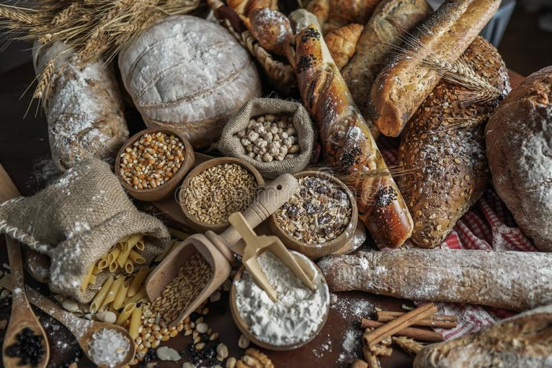 Bread background. Brown and white whole grain loaves wrapped in kraft paper composition on rustic dark wood with wheat ears scatte royalty free stock photography