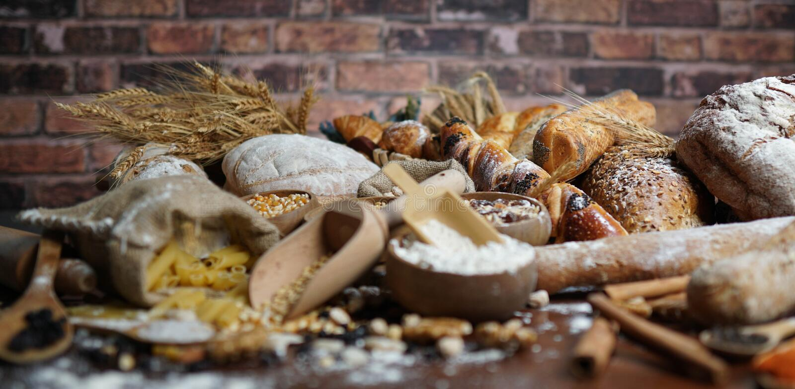 Bread background. Brown and white whole grain loaves wrapped in kraft paper composition on rustic dark wood with wheat ears scatte stock photo