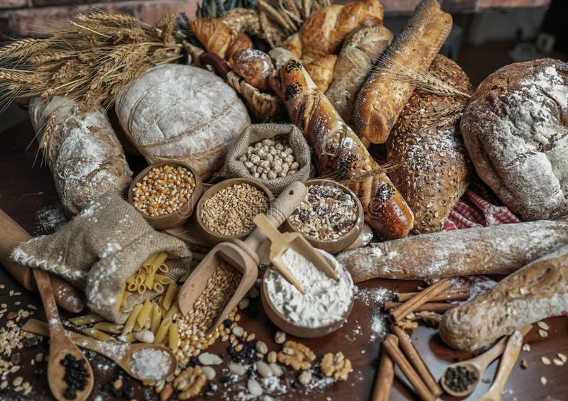 Bread background. Brown and white whole grain loaves wrapped in kraft paper composition on rustic dark wood with wheat ears scatte royalty free stock image