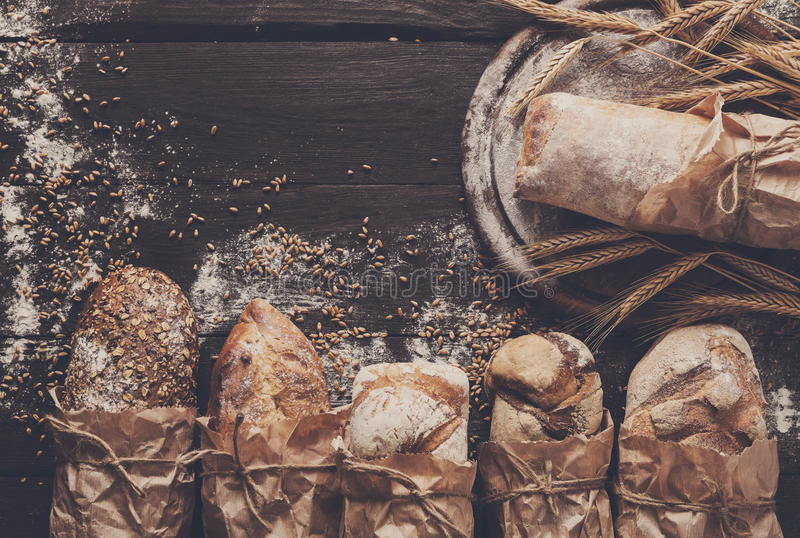 Bread bakery background. Brown and white wheat grain loaves composition. Bread background. Brown and white whole grain loaves wrapped in kraft paper composition stock photo