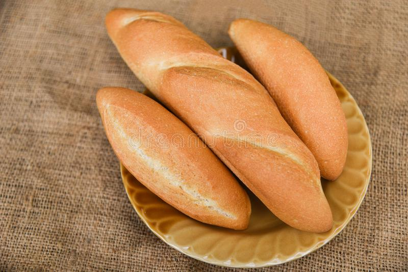 Bread and buns assortment / Fresh Bakery bread various types on plate with sack background / homemade breakfast food stock photos