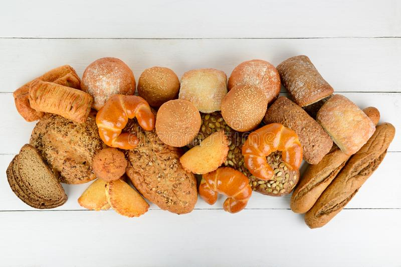 Bread, buns, croissants and other baked goods on wooden table. Top view. Copy space stock photography