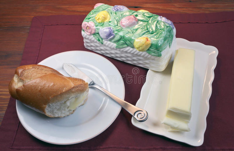 Bread and Butter. Bread on a plate with butter knife and Butter on a butter dish with floral cover royalty free stock image