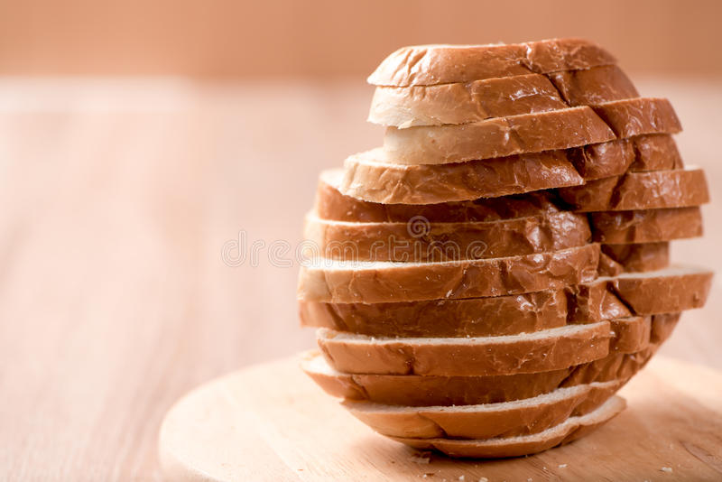 Bread on chopping block in wood background stock image