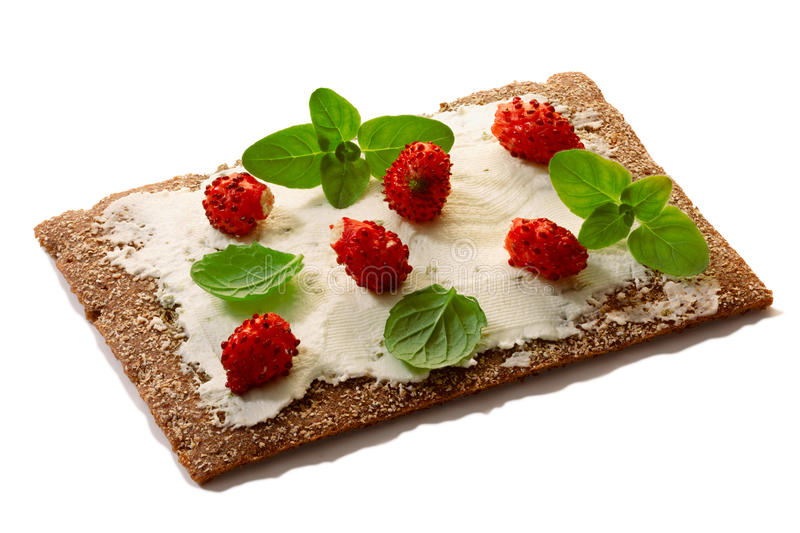 Bread crisp with fresh strawberries, soft cheese and mint. Bread crisp (crispbread open-faced sandwich) with field strawberries, soft cream cheese, mint and royalty free stock photo