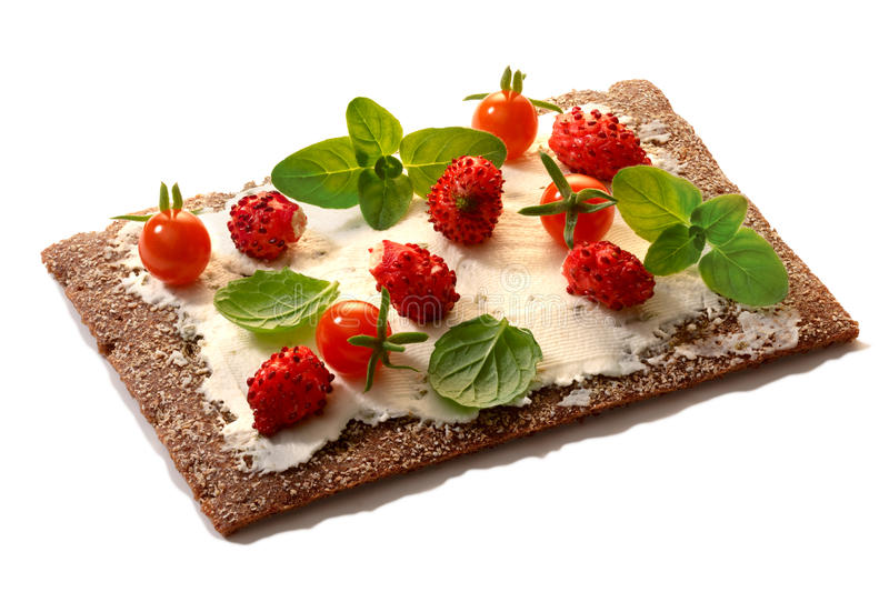 Bread crisp with fresh strawberries, soft cheese and mint. Bread crisp (crispbread open-faced sandwich) with field strawberries, currant tomatoes, soft cream royalty free stock image