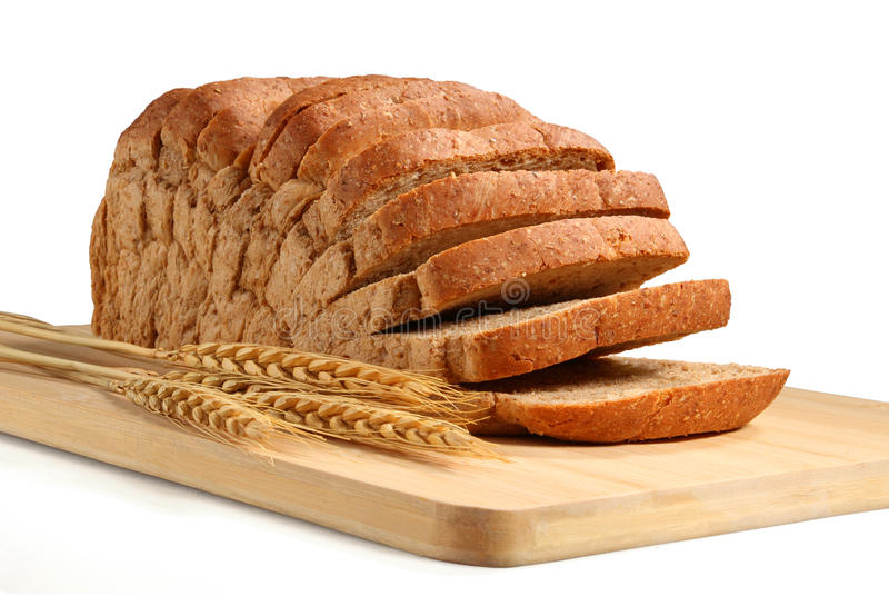 Bread cut. With wheat on wooden board stock photo