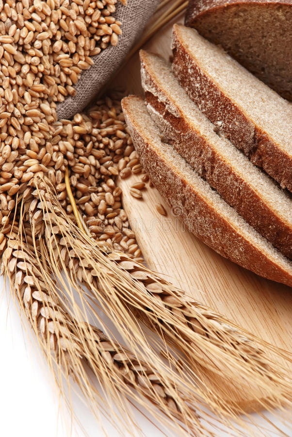 Bread cut on a board and a bag with wheat. Bread cut on a board, a bag with wheat and ear of the wheat on a white background stock image