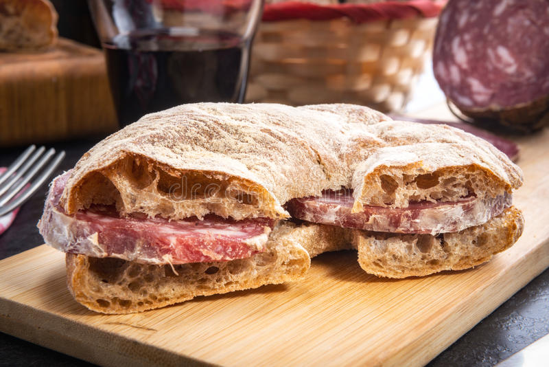 Bread cut and filled with Italian salami. Bread of Valtellina cut and filled with Italian salami served on a wooden board accompanied by red wine stock image