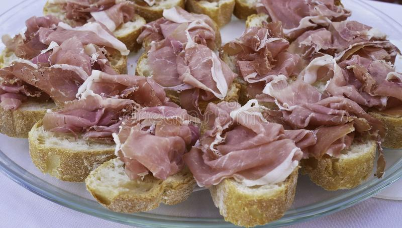 Bread cut into slices with raw ham of san daniele royalty free stock photos