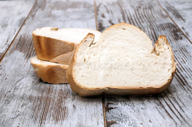 Bread cut. Surrounded by rustic background royalty free stock photography