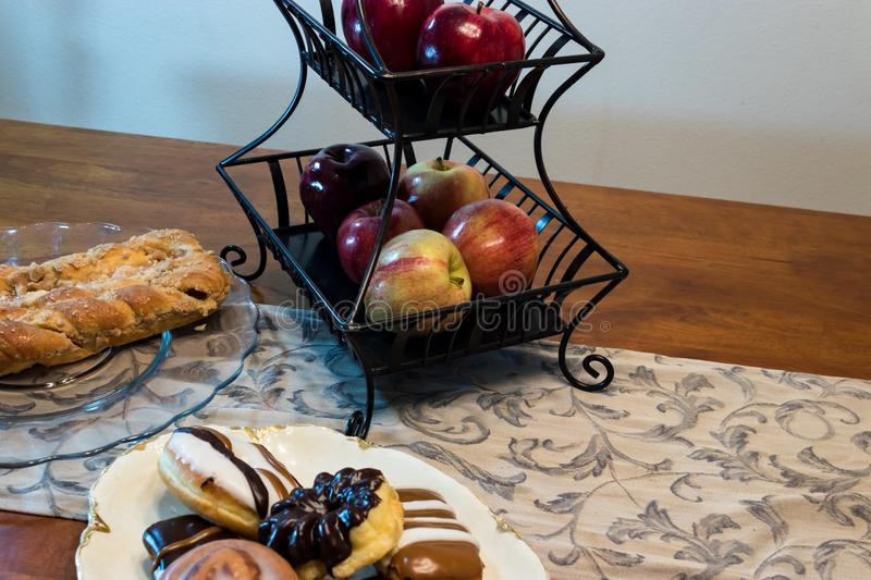 Bread donuts and fruit. Bread and donuts on a table with runner near a basket of apples stock image