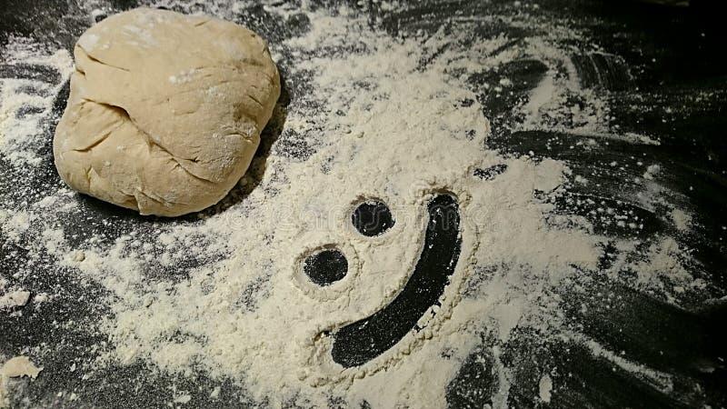 Bread dough with a smiley face in flour. stock photos