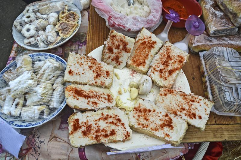 Bread with fats, ground pepper and garlic. Traditional Banat is served with fats and sprinkled with red pepper with white onions and homemade cakes on offer stock photo