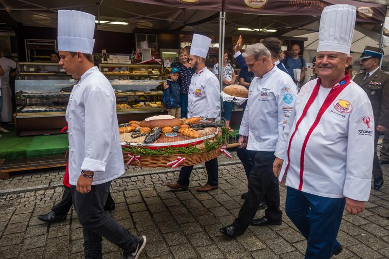 Bread and Gingerbread Festival parade. Jawor, Poland - July 2018 : Bakers dressed in white working outfits carrying wicker basket with breads during parade on stock photo