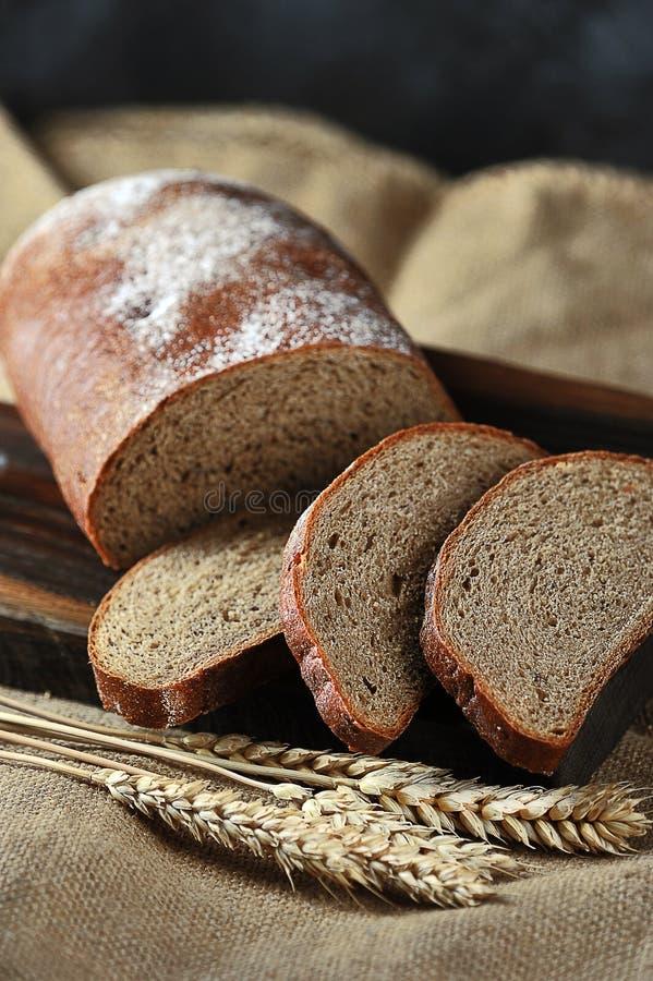 Bread and grain ears on burlap stock photos
