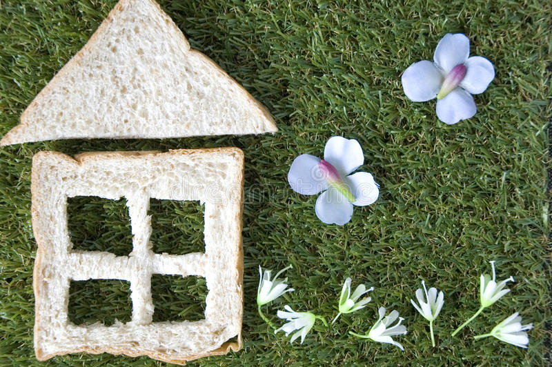 Bread house with garden. Bread cut in house shape with garden flowers royalty free stock photos