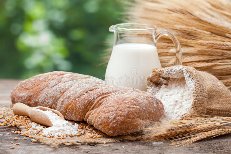 Bread, jug of milk, sack with flour and sheaf of wheat royalty free stock photo