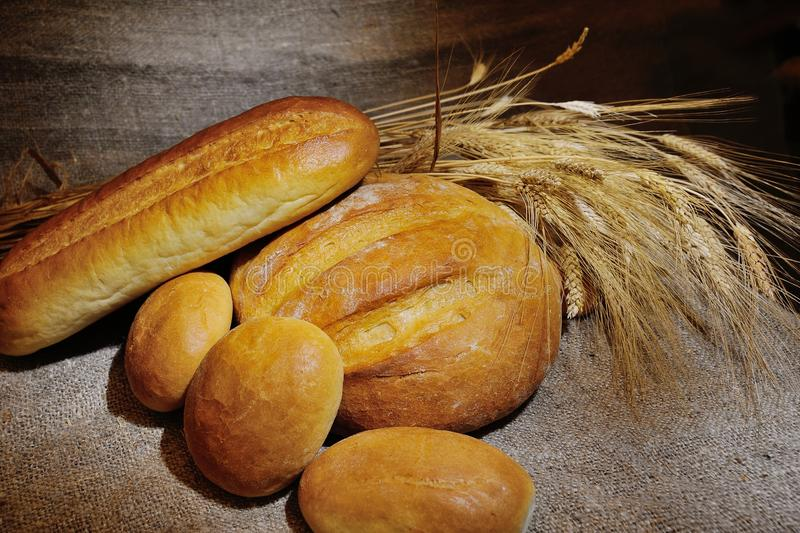 Bread, loaf, white bread, wheat ears on a background of burlap stock photos