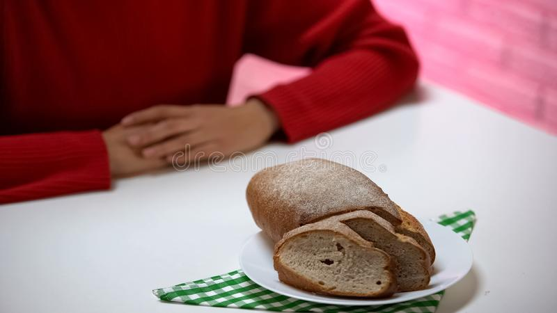 Bread lying on plate, woman sitting at table, refusing to eat high calorie food stock photo
