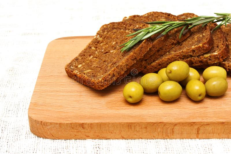 Bread, olives, rosemary and wooden board