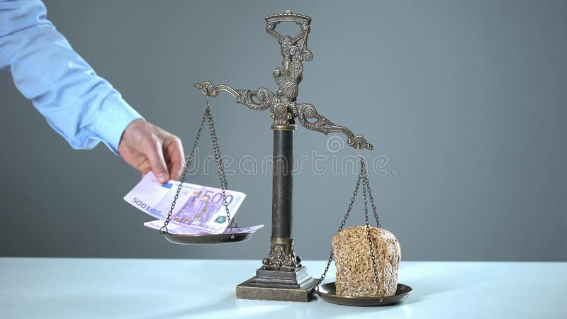 Bread outweighs euro on scales, poverty concept, poor people more than rich royalty free stock images
